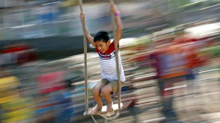 নেপালের কাঠমুণ্ডুতে দোলনায় দোল খাচ্ছে এক শিশু